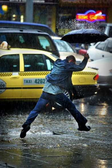 csz030413.001.001.jpg The Age NEWS  Lonsdale street Melbourne, the heavens open up with rain as a man with a umbrella tries to leap water running down a driveway. 13th April 2003. S Picture By Craig Sillitoe